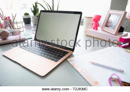 Laptop rosa e cornice immagine sulla scrivania Immagini Stock