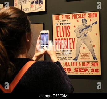 """Aprile 20, 2019 - New York, New York, Stati Uniti - Un museo goer prende la foto di un Elvis Presley concert poster sul display in """"Play forte: Strumenti di Rock and Roll' presentano presso il Metropolitan Museum of Art. (Credito Immagine: © Nancy Kaszerman/ZUMA filo) Immagini Stock"""
