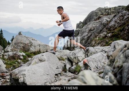 L'uomo escursionismo, saltare attraverso le rocce, cane montagna, BC, Canada Immagini Stock