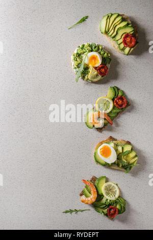 Varietà di panini vegetariani con fette di avocado, pomodori secchi, uovo, gamberetti, rucola servita su bianco grigio Sfondo maculato. Piatto, laici s Immagini Stock