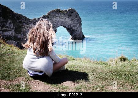 Ragazza sedeva dalla porta di Durdle,Dorset,l'Inghilterra,UK Immagini Stock