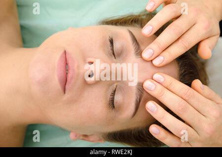 Donna su spa trattamenti di massaggi in beauty spa salone. Cosmetologo rendendo ragazza rilassante massaggio viso e testa. Estetista medico e paziente. Pelle Spa Immagini Stock