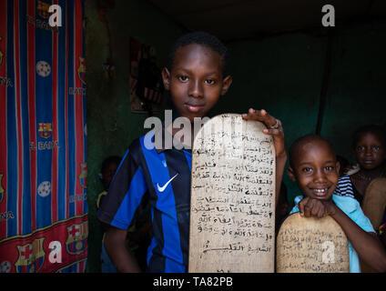 I bambini con pannelli di legno per la scrittura di corano in una scuola coranica, Regione Tonkpi, uomo, Costa d'Avorio Immagini Stock