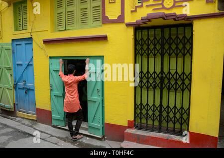 Uomo in piedi fuori casa colorati, Calcutta, West Bengal, India, Asia Immagini Stock