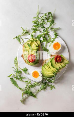 Sandwich vegetariano con fette di avocado, pomodori secchi, uovo, rucola servita sulla scheda di ceramica su marmo bianco dello sfondo. Laici piana, spazio Immagini Stock