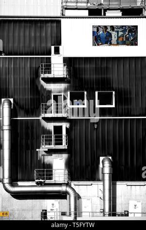 Il collage di un edificio industriale con workshop e tubi di ventilazione con il mosaico dipinto 'Man vince il cosmo' di FRITZ EISEL. Immagini Stock