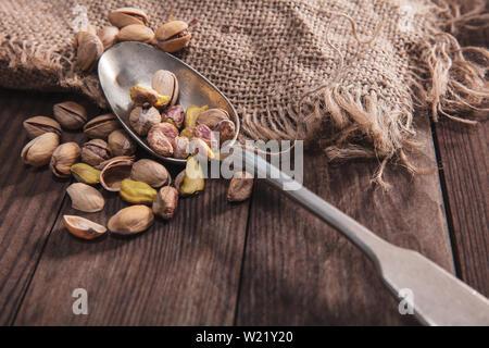 I pistacchi su un vecchio cucchiaio e composizione dal vecchio legno e materiali Immagini Stock