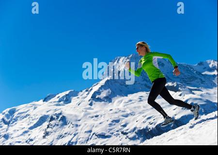 Una donna fare jogging in alta innevate montagne alpine. Immagini Stock
