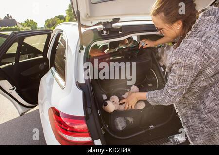 Donna giocattoli di imballaggio nel baule auto Immagini Stock