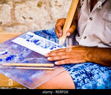 Artista seduto fuori mura della vecchia città di Dubrovnik pittura con canne di bambù. La vendita di opere d'arte di turisti. © Myrleen Pearson ...Ferguson Cate Immagini Stock