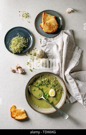 Iniziato mangiato verde zuppa di verdure asparagi, broccoli o pisello, decorata da pisello verde, germogli di soia e uova di quaglia in ciotole di ceramica con pane, sale e pe Immagini Stock