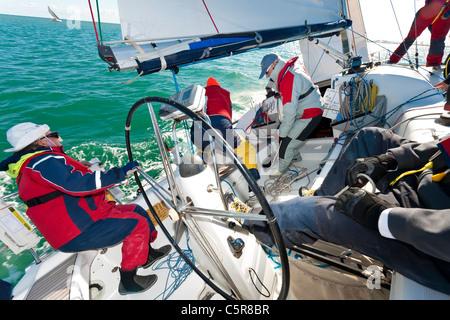 Un yacht offshore racing equipaggio vela occupato sull'oceano. Immagini Stock