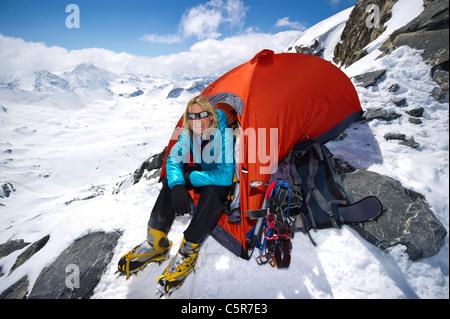 Un alpinista seduto in tenda su alta sulle alte montagne innevate. Immagini Stock