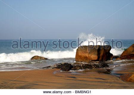 Spruzzi delle onde sulla roccia a Kovalam Beach, Kerala Immagini Stock