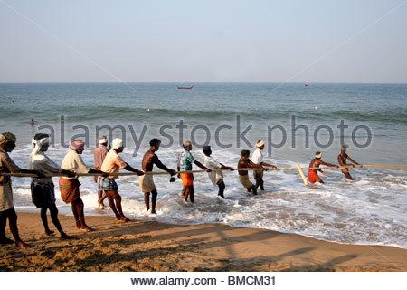 Gruppo di pescatori al lavoro a Kovalam Beach, Kerala Immagini Stock
