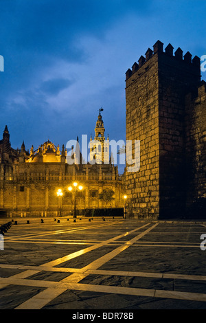 La torre Giralda e la cattedrale sulla sinistra al crepuscolo con pareti di Alcazar sulla destra, Siviglia, Spagna Immagini Stock