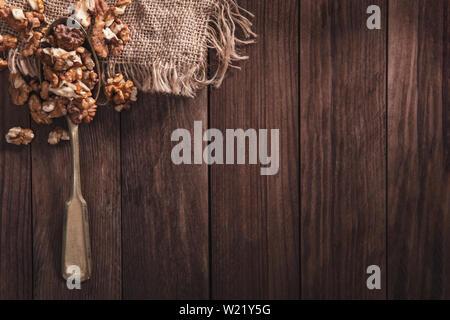 Le noci su un vecchio cucchiaio e composizione dal vecchio legno e materiale. Vista superiore e spazio vuoto sul lato destro per il testo Immagini Stock