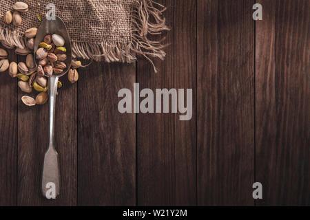 I pistacchi su un vecchio cucchiaio e composizione dal vecchio legno e materiale. Vista superiore e spazio vuoto sul lato destro per il testo Immagini Stock