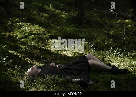 Ombre sulla donna caucasica posa in erba Immagini Stock