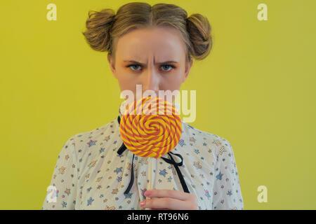 Ritratto di un funny girl tenendo un arancio lecca-lecca di fronte faccia su sfondo lucido Immagini Stock