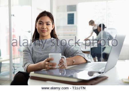 Ritratto fiducioso imprenditrice di bere il caffè al computer portatile in ufficio Immagini Stock