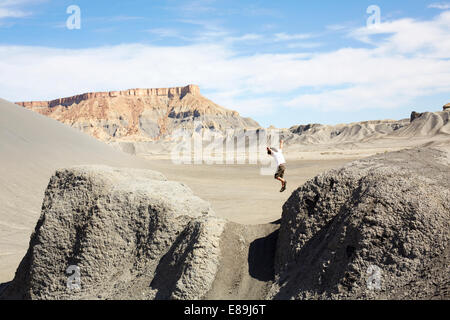 Ragazzo che salta da rocce nel deserto Immagini Stock