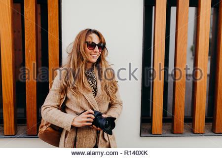 Una giovane donna con capelli bruna indossando occhiali da sole all'aperto Immagini Stock