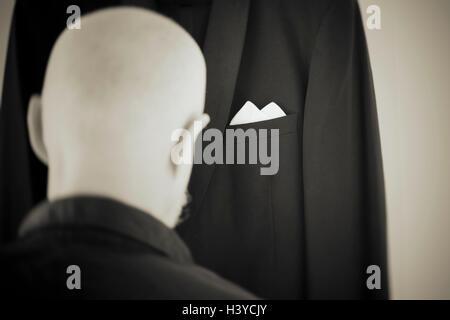 Il vecchio uomo vestirsi in abito formale. Vista posteriore verticale. Momento di stile di vita della persona in Immagini Stock