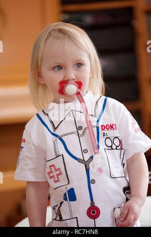 Ragazza bionda con succhietto indossando il costume di medici Immagini Stock