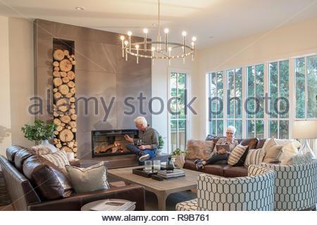 Coppia senior rilassante da caminetto in soggiorno Immagini Stock