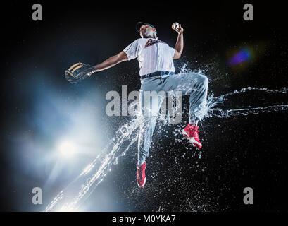 Spruzzi d'acqua su jumping black giocatore di baseball Immagini Stock