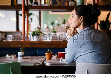 Considerato giovane donna presso il cafe tabella Immagini Stock