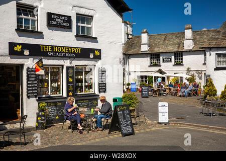 Regno Unito, Cumbria, Hawkshead, il Quadrato, coppia di bere il caffè di mattina al di fuori del negozio Honeypot e café acress quadrato dal menestrello's Galleria cafe Immagini Stock