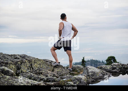 Escursionista maschio in appoggio sulla montagna, cane montagna, BC, Canada Immagini Stock