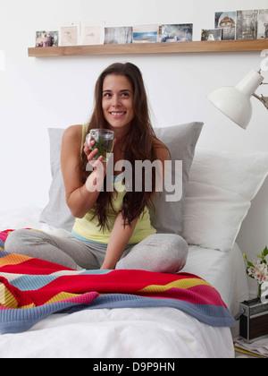 Bruna giovane donna bere il tè sul letto Immagini Stock