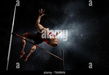 Via maschio e atleta di campo ad alta jumping Immagini Stock