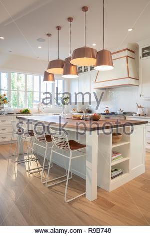 Casa bianca di vetrina cucina interna con rame le luci pendenti Immagini Stock