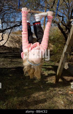 Una giovane ragazza appeso a testa in giù da uno swing Immagini Stock