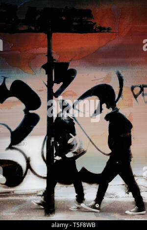 Una giovane coppia di passeggiate nel quartiere arabo Barbes a Parigi e passa i graffiti. Immagini Stock