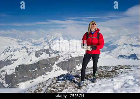 Una donna in alta montagna innevata utilizzando una cartina e bussola per l'orientamento. Immagini Stock