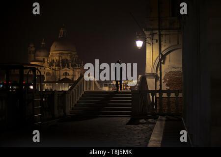 Silhouette di un uomo a piedi attraverso le strade di notte, Venezia, Veneto, Italia Immagini Stock