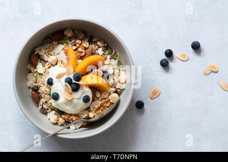 Ciotola di muesli fatti in casa con pesche tagliate a fette, yogurt e mirtilli. Immagini Stock