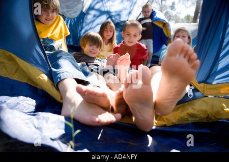 Una donna e un gruppo di bambini ammucchiati in una tenda Immagini Stock
