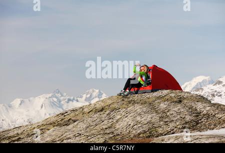Una donna in campeggio in alta montagna innevata liquido potabile da ri-idrato. Immagini Stock