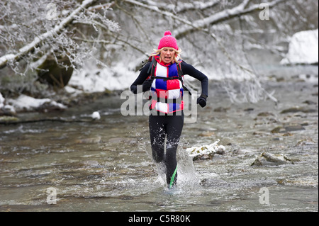 Un pareggiatore in esecuzione attraverso un snowy il letto del fiume e fredde acque alpine. Immagini Stock