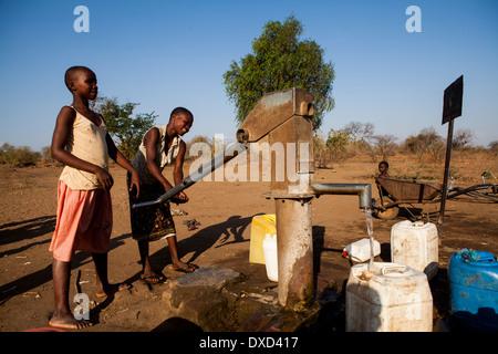 Africa bambini raccolta di acqua in un tubo di supporto Immagini Stock