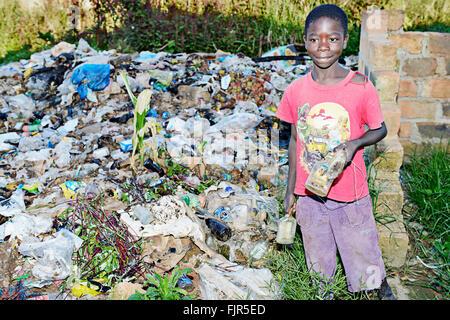 Piccolo Ragazzo la raccolta di rifiuti in una discarica di rifiuti in Manyama, Zambia. Immagini Stock