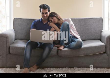 Coppia giovane seduto sul divano utilizzando portatile a casa Immagini Stock