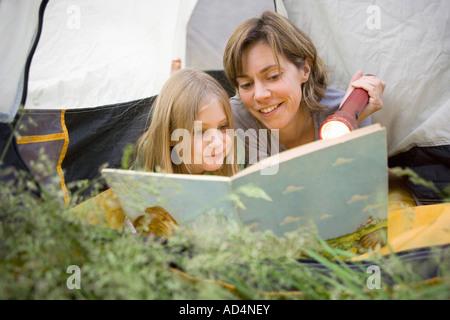 Una madre e figlia che spuntavano di una tenda e la lettura insieme Immagini Stock