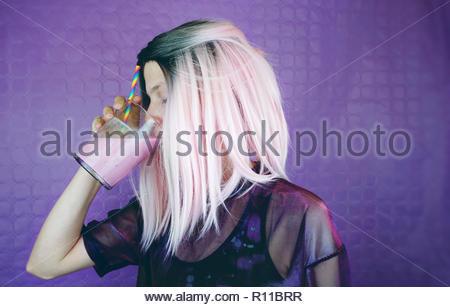 Ritratto di una donna di bere contro uno sfondo viola Immagini Stock